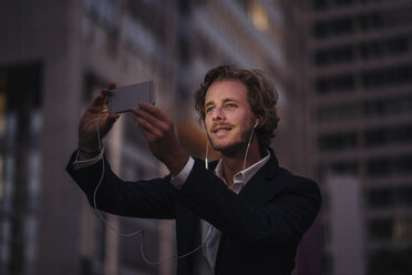 Businessman in the city at dusk with cell phone and earphones - KNSF00992