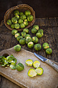 Brussels sprouts, kitchen knife and wooden board on dark wood - LVF05839