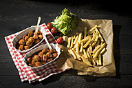 Two bowls of Currywurst and French fries on baking paper - MAEF12105