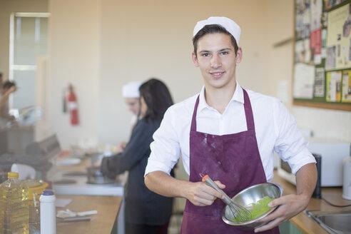 Portrait of teenage boy in cooking uniform in high school class - ZEF12636