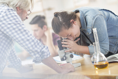 Science student with teacher in class looking through microscope - ZEF12648