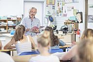 Teacher in class holding booklet - ZEF12651