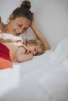 Mother and little daughter cuddling in bed - DWF00256