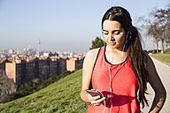 Female athlete with earphones using her phone - ABZF01835