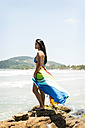 Brasil, Sao Paulo, Ubatuba, young woman standing on a rock at the beach - VABF01093
