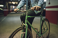 Man with his fixie bike in a garage - RAEF01717