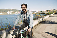Smiling young man riding his fixie bike at the waterfront - RAEF01723