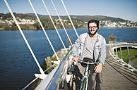 Smiling young man with his fixie bike on a bridge - RAEF01726