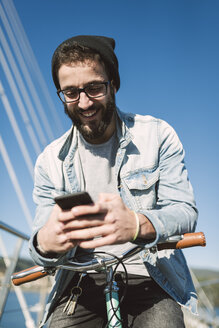 Smiling young man with fixie bike using a smartphone on a bridge - RAEF01729