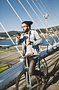 Young man with fixie bike on a bridge using smartphone - RAEF01732