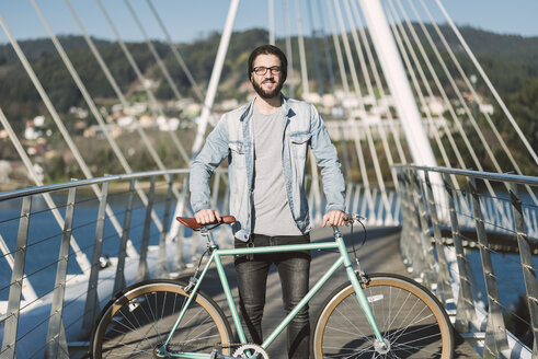 Smiling young man with his fixie bike on a bridge - RAEF01735