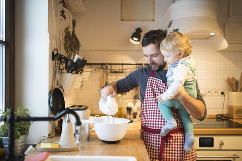 Father and baby boy in kitchen baking a cake - HAPF01335