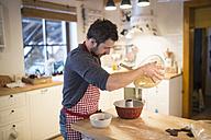 Man standing in kitchen baking ring cake - HAPF01341
