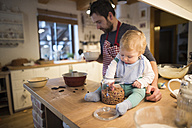 Father and baby boy in kitchen baking a cake - HAPF01344