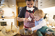 Father and baby boy in kitchen baking a cake - HAPF01347