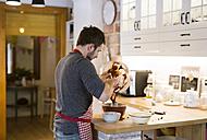 Man standing in kitchen baking ring cake - HAPF01350