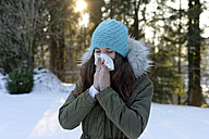 Teenage girl wearing woolly hat blowing her nose in winter - LBF01547