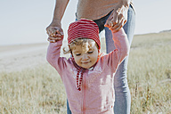 Smiling toddler holding mother's hands on a meadow - DWF00271