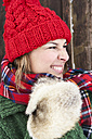 Portrait of woman wearing red bobble hat and fur gloves in winter - FSF00738