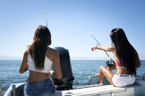Two young women fishing on a boat trip - ABAF02146