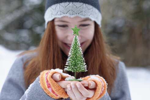 Teenage girl holding little Christmas tree - LBF01552