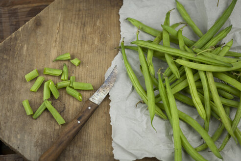 Whole and chopped green beans and kitchen knife on paper and wooden board - JUNF00825