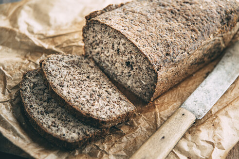 Home-baked wholemeal glutenfree bread and bread knife on brown paper - IPF00354