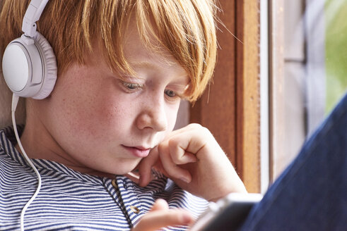 Boy sitting on window sill using digital tablet, wearing head phones - JEDF00279