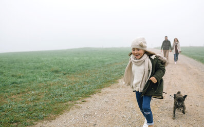 Happy girl running with her dog while her parents walking in the background on a foggy day in winter - DAPF00553