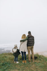 Family with dog at the coast on a foggy winter day looking at view - DAPF00556