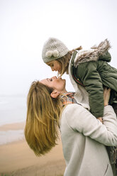 Woman lifting up and kissing daughter on the beach in winter - DAPF00559