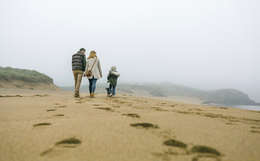 Family walking with dog on the beach on a foggy winter day - DAPF00562
