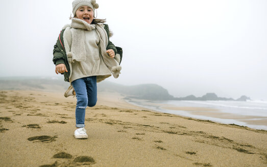 Happy girl running on the beach on a foggy winter day - DAPF00565