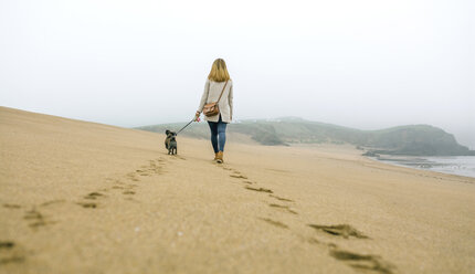 Woman walking with dog on the beach in winter - DAPF00568
