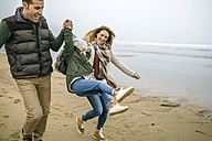Happy parents lifting up daughter on the beach in winter - DAPF00571