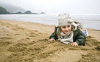 Happy girl lying in sand on the beach in winter - DAPF00574