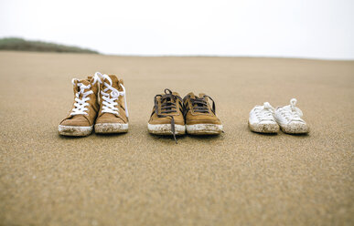 Three pairs of shoes with different sizes on the beach - DAPF00583