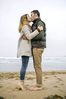 Couple standing barefoot on the beach kissing - DAPF00586