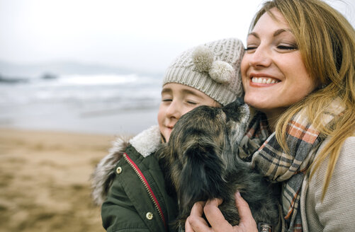 Mother and daughter hugging their dog on the beach in winter - DAPF00592