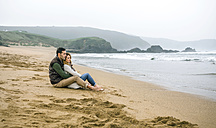 Couple in love sitting on the beach in winter - DAPF00595