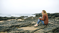 Lonely woman sitting on rocks on the beach in winter - DAPF00601
