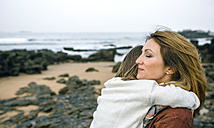 Mother holding daughter on the beach in winter - DAPF00604