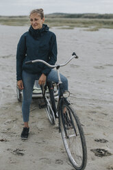 Netherlands, Schiermonnikoog, woman with bicycle and trailer on the beach - DWF00286