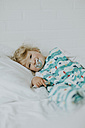 Little girl with pacifier lying in bed - DWF00289
