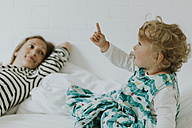 Little girl with mother in bed pointing her finger - DWF00292
