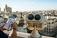 Spain, Madrid, close-up of binoculars and man holding book with cityscape in background - KIJF01177