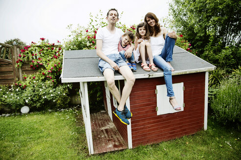 Happy family sitting on roof of their garden shed - JATF00961