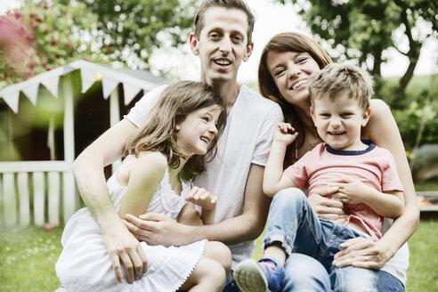 Happy family sitting in garden - JATF00967