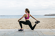 Young woman stretching and warming up for training at the beach - GIOF01730