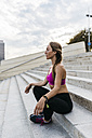 Young woman sitting on stairs after training - GIOF01742